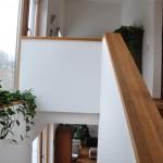 Die Treppe verbindet zwei offene Wohnbereiche: unten das Wohnzimmer, oben den Flur. Mit zwei großen Fenstern wirken auch Treppe und Flur hell und luftig.