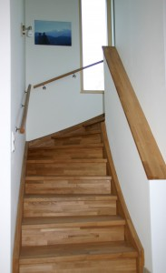 Eine Holztreppe führt ins Obergeschoss.