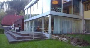 Fassade des Mühltalhofs mit Glasanbau und Kortenstahl.