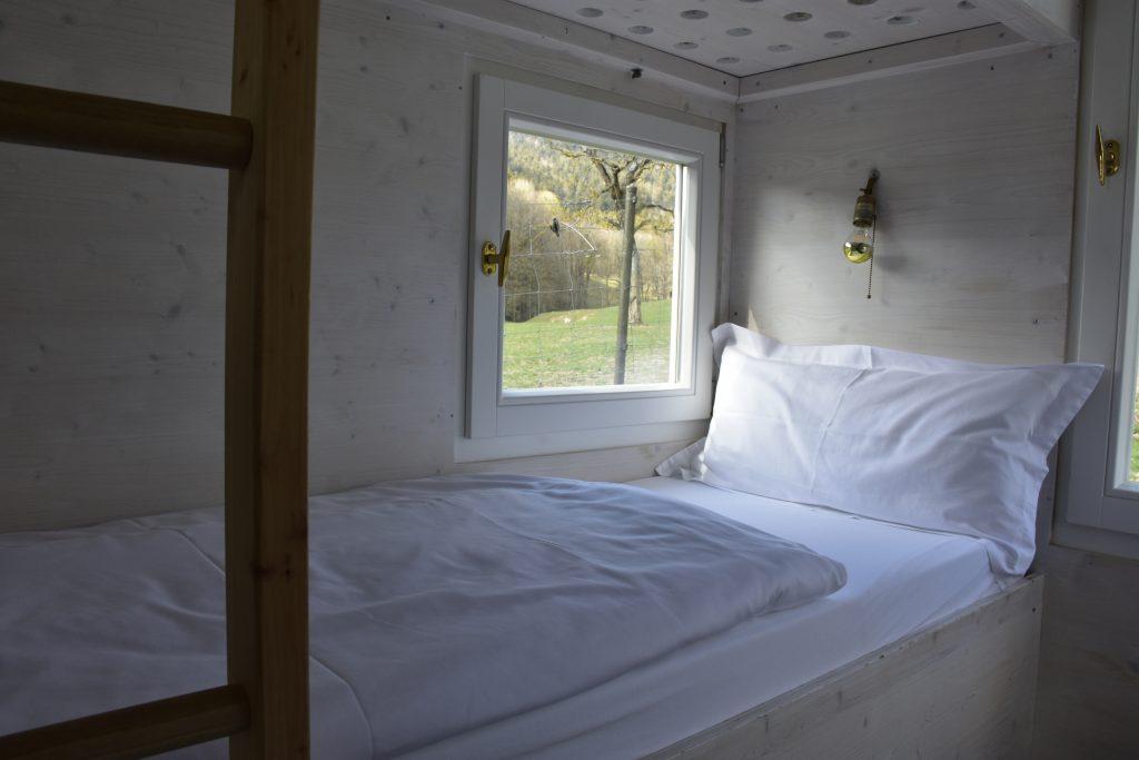Blick auf das kojenartige Bett in der HYT mit kleinem Fenster neben dem Kopfteil.
