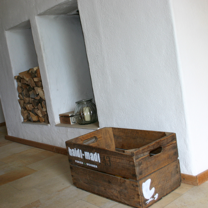 Im Flur steht eine Holzkiste mit dem Schriftzug von Haidl-Madl Ferienwohnen
