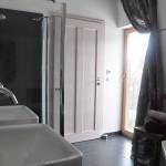 Das Badezimmer hat ebenfalls eine schräge und bis zum First offene Decke. Es hat aber das kleinste Fenster. Ein bisschen Privatsphäre muss sein.