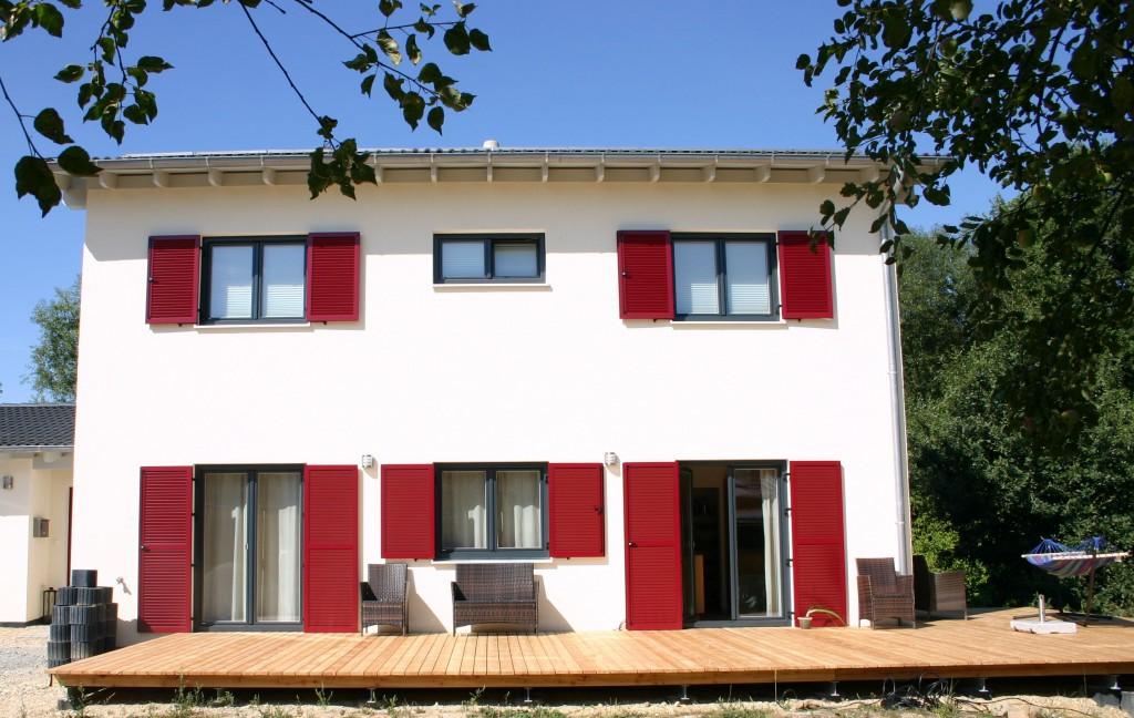 Das Einfamilienhaus mit roten Fensterläden und Terrasse.