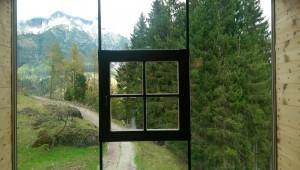 Blick nach draußen durch eine Glasscheibe im Hotel Forsthofalm.
