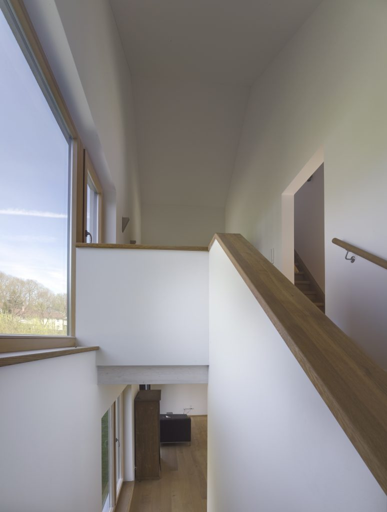 Blick vom Podest in der Mitte der Treppe nach oben und unten. Hier wird deutlich, dass die Verbindung zwischen Erdgeschoss und Obergeschoss zwar offen, aber nicht komplett einsehbar gestaltet wurde.